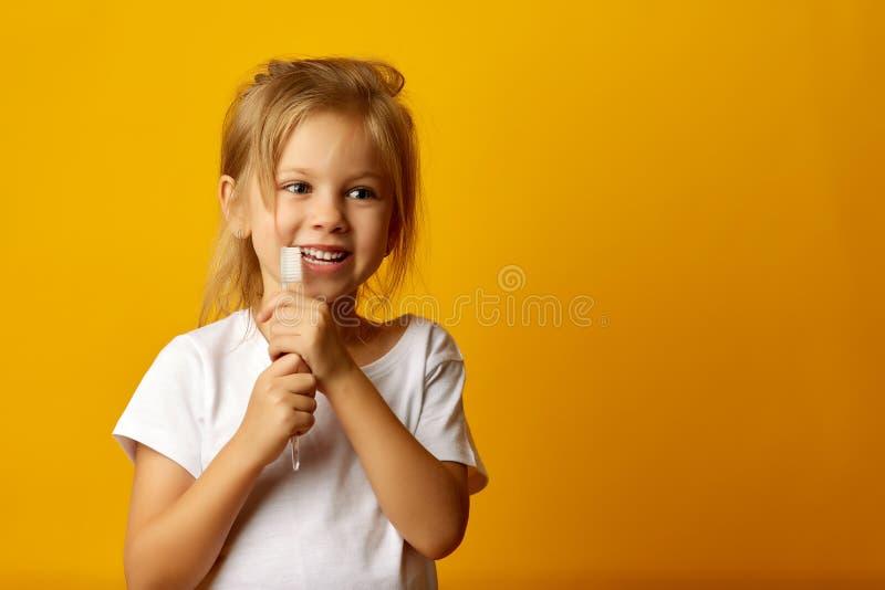 Förtjusande flicka som borstar tänder med ungetandborsten arkivbild