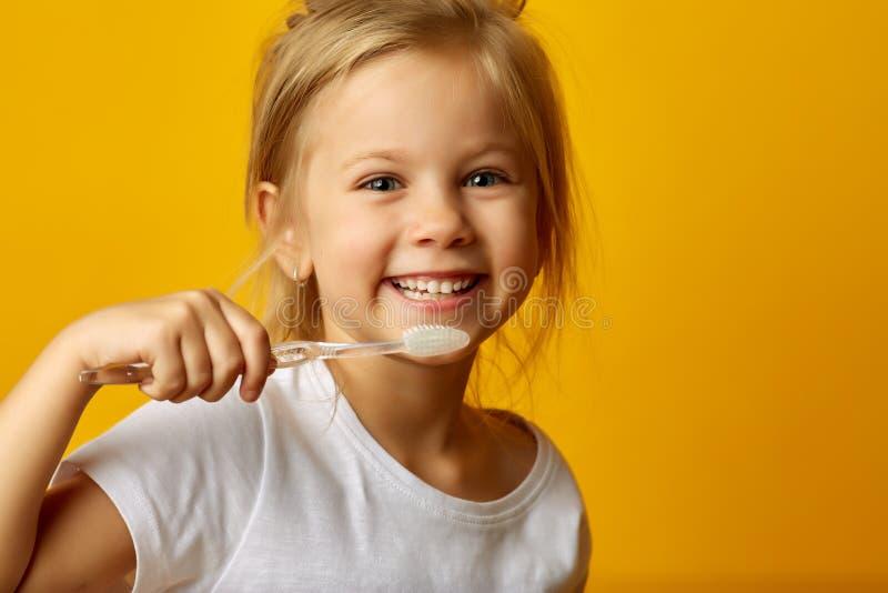 Förtjusande flicka som borstar tänder med ungetandborsten royaltyfria bilder