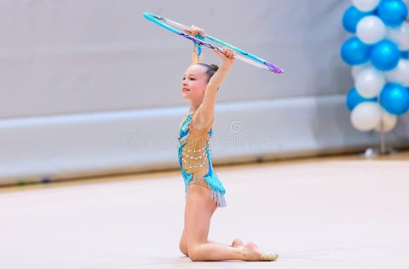 Förtjusande flicka som konkurrerar i rytmisk gymnastik royaltyfri foto