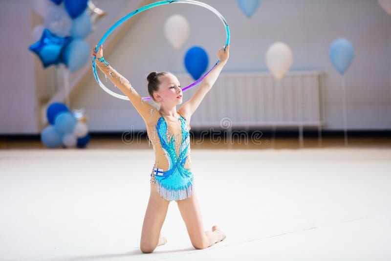 Förtjusande flicka som konkurrerar i rytmisk gymnastik royaltyfri bild