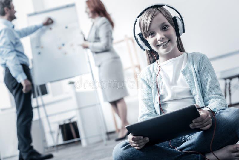 Förtjusande flicka som ler medan listeninf till mucis arkivfoton