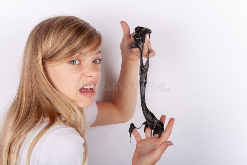 Förtjusande flicka som rymmer en svart slam och framställning royaltyfri fotografi