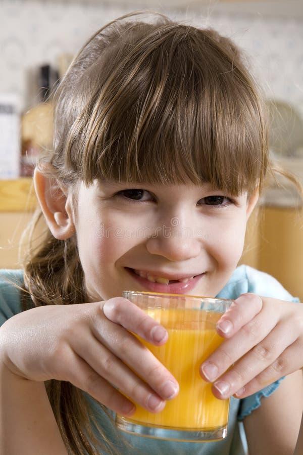 förtjusande gullig drinkflickafruktsaft little som är orange fotografering för bildbyråer