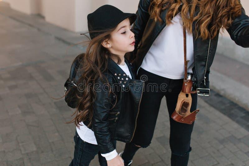 Förtjusande gullig flicka med skolapåsen som ser stå bort bredvid moder med den retro kameran Utomhus- stående av slankt lockigt arkivbilder