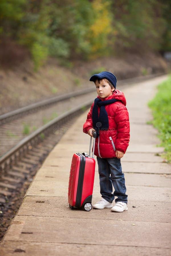 Förtjusande gulligt litet barn, pojke som väntar på en järnvägsstation fo royaltyfri bild