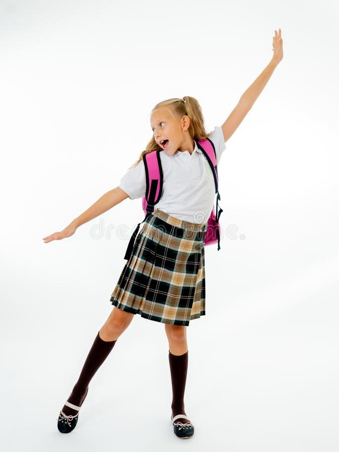 Förtjusande härlig liten skolflicka med den stora rosa skolväskan som känner sig upphetsat och lyckligt vara tillbaka till skola  arkivbild