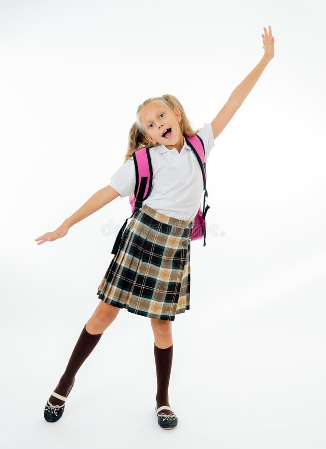 Förtjusande härlig liten skolflicka med den stora rosa skolväskan som känner sig upphetsat och lyckligt vara tillbaka till skola  arkivfoton