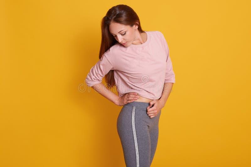 Förtjusande kvinna med den perfekta kroppen i sportkläder som isoleras över gul studiobakgrund, sportig attraktiv kvinnlig som se arkivbild