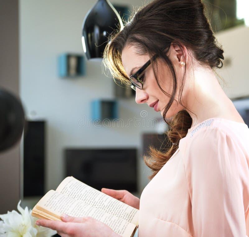 Förtjusande kvinna som läser en roman fotografering för bildbyråer