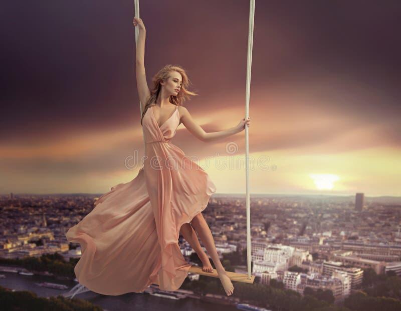 Förtjusande kvinna som svänger ovanför staden
