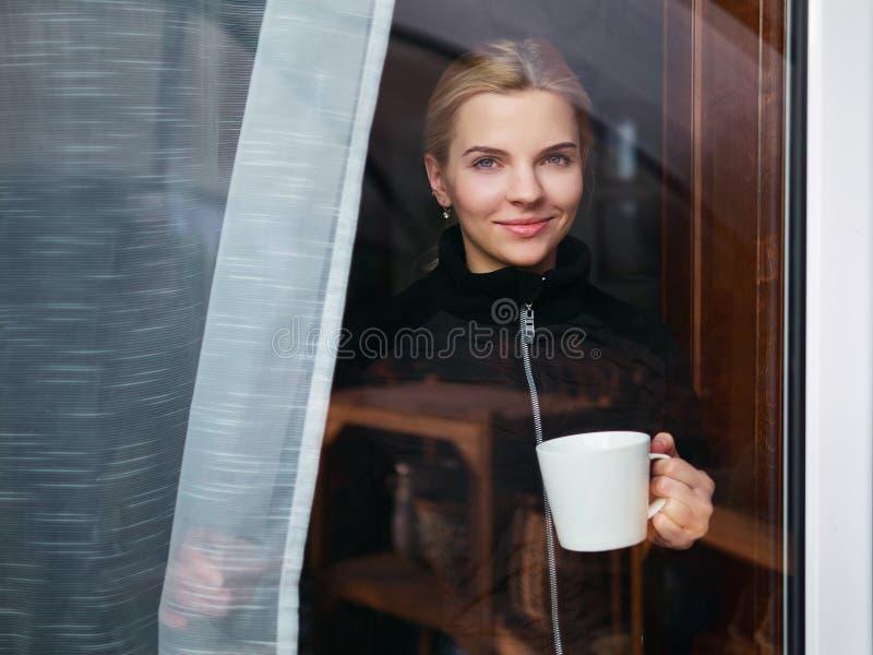 Förtjusande kvinna som ut ser till och med ett fönster och rymmer en kopp kaffe eller ett te Härlig och fundersam blondin med loc arkivbild