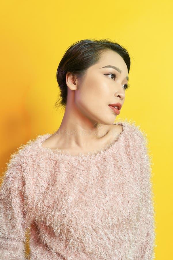 Förtjusande kvinna som uttrycker riktiga positiva sinnesrörelser under photoshoot i rosa pälslag Inomhus stående av den aktiva gl arkivfoto