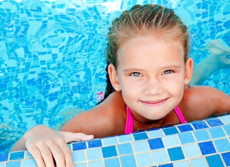 Förtjusande le liten flicka i simbassäng arkivbild