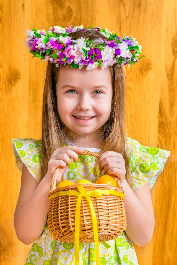Förtjusande le liten flicka med långt blont hår som bär den blom- head vide- korgen för krans och för innehav med gula ägg royaltyfri foto