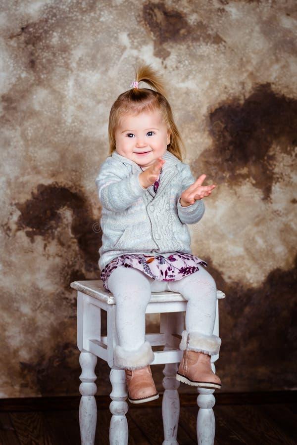 Förtjusande le liten flicka med sammanträde för blont hår på stol fotografering för bildbyråer
