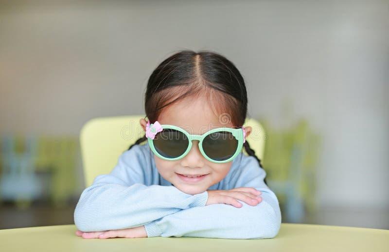Förtjusande liten asiatisk barnflicka som lägger på exponeringsglas för sol för barntabell bärande med att le och att se kameran, fotografering för bildbyråer