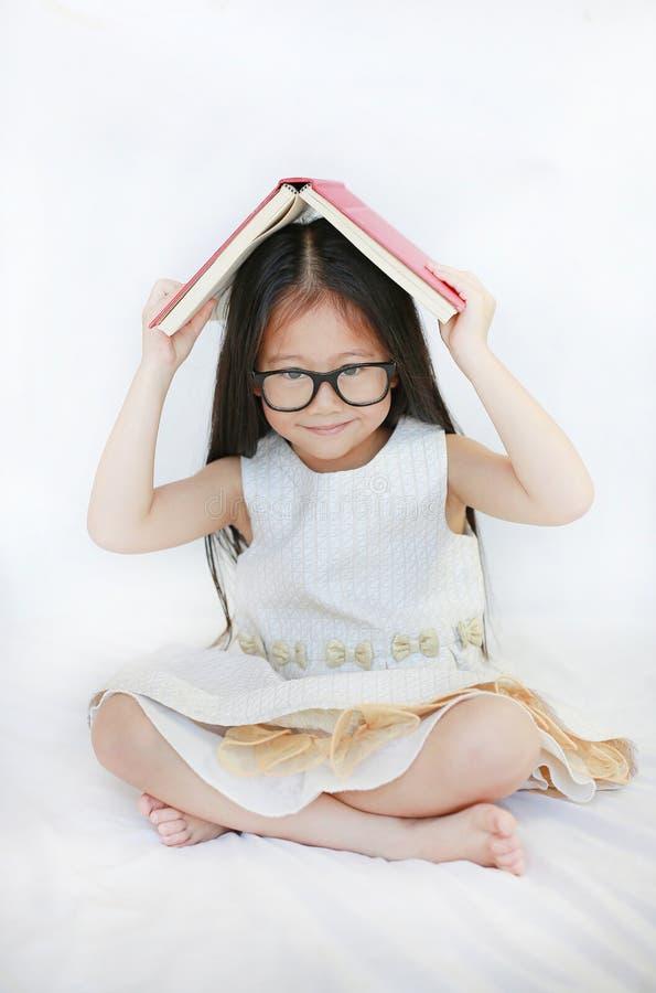 Förtjusande liten asiatisk flicka som ligger på säng- och ställehardcoverboken på hennes huvud och ser kameran över vit bakgrund arkivfoto