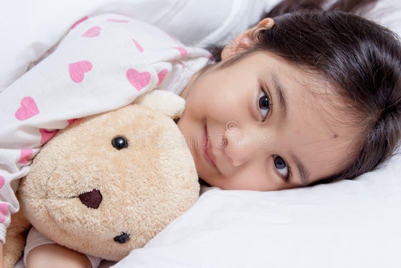 Förtjusande liten asiatisk flickasömn med björndockan arkivfoto