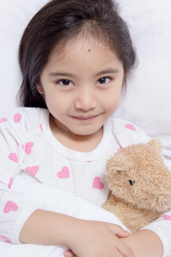 Förtjusande liten asiatisk flickasömn med björndockan fotografering för bildbyråer