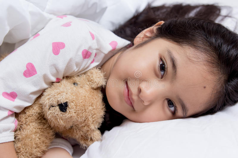 Förtjusande liten asiatisk flickasömn med björndockan arkivbilder
