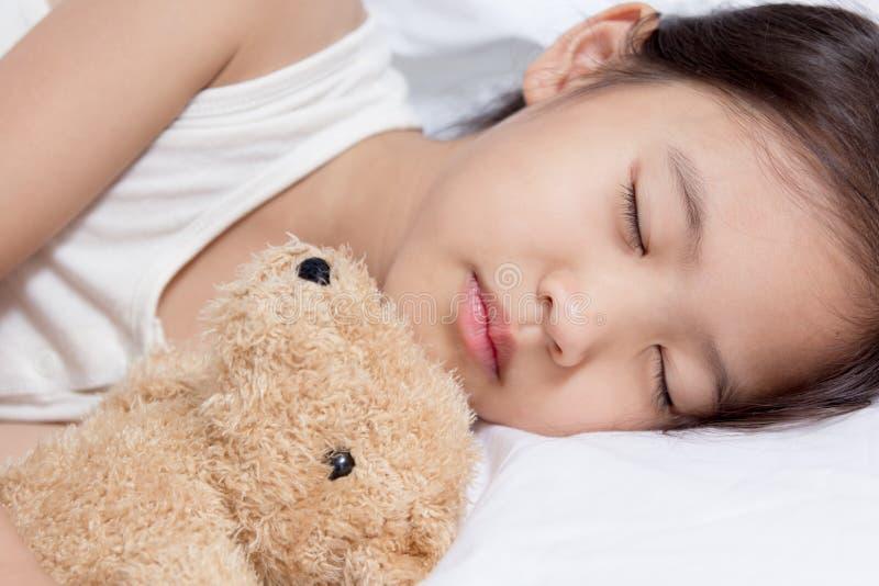 Förtjusande liten asiatisk flickasömn på hennes säng med björndockan arkivfoto