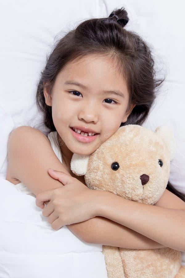 Förtjusande liten asiatisk flickasömn på hennes säng med björndockan arkivbilder