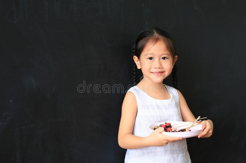 Förtjusande liten asiatisk platta för barnflickainnehav av hemlagade chokladdonuts mot svart tavlabakgrund arkivfoton
