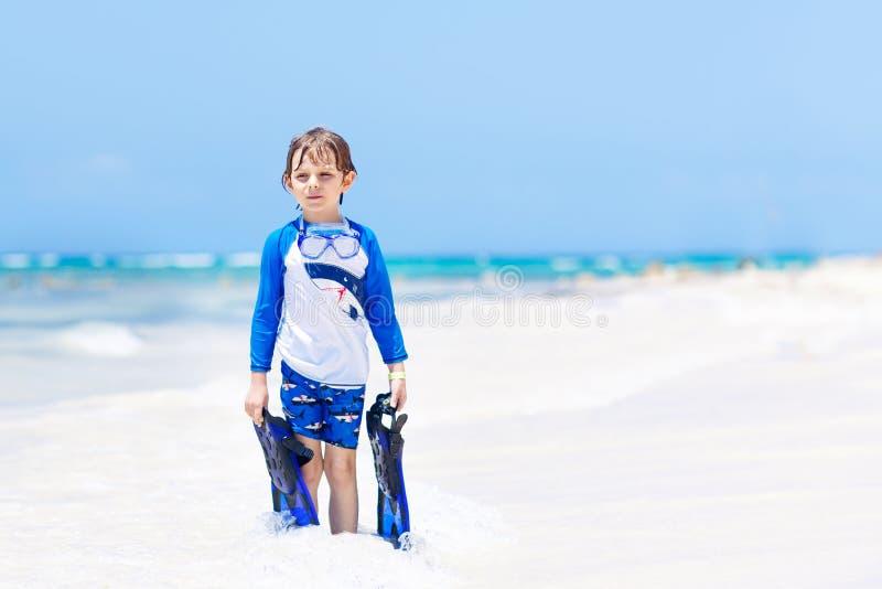 Förtjusande liten blond ungepojke som har gyckel på den tropiska stranden av Maldiverna Upphetsat barn som spelar och surfar i so royaltyfria foton