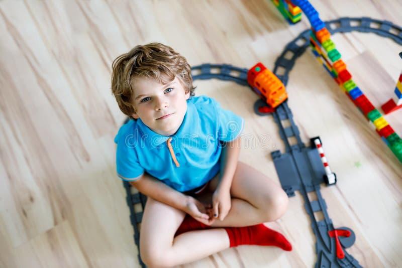 Förtjusande liten blond ungepojke som spelar med färgrika plast- kvarter och skapar drevstationen Barn som har gyckel med royaltyfri bild
