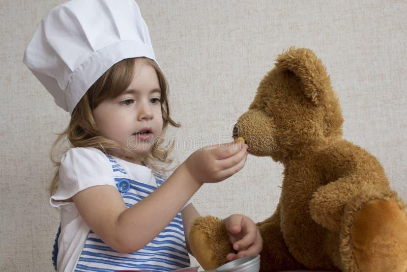 Förtjusande liten flicka för stående i kockhatt behandla som ett barn matningar en leksakbjörn royaltyfri fotografi