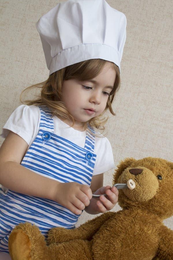 Förtjusande liten flicka för stående i kockhatt behandla som ett barn matningar en leksakbjörn arkivbilder