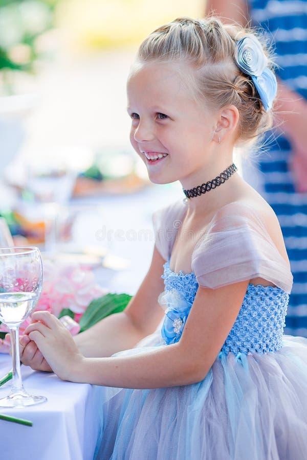 Förtjusande liten flicka i fantastisk klänning på en bröllopceremoni utomhus royaltyfri bild
