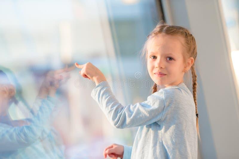 Förtjusande liten flicka i flygplats nära det stora fönstret som ser stort flygplan arkivbilder