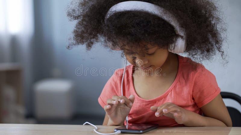 Förtjusande liten flicka med hörlurar med mikrofon på att lyssna till musik som beskådar foto på telefonen arkivfoton