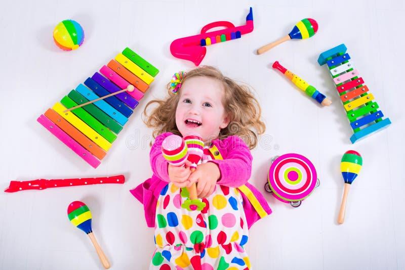 Förtjusande liten flicka med musikinstrument royaltyfria bilder