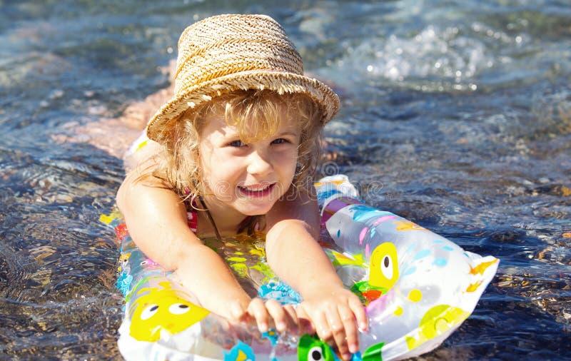 Förtjusande liten flicka på luftuppblåsbarmadrassen arkivfoto