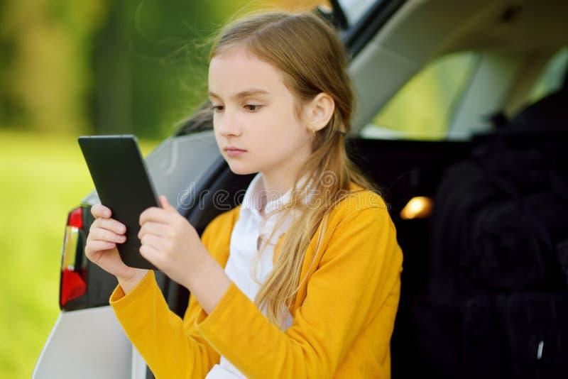 Förtjusande liten flicka som är klar att gå på semestrar med hennes föräldrar Lura sammanträde i en bilstam och läsning hennes eb arkivfoton
