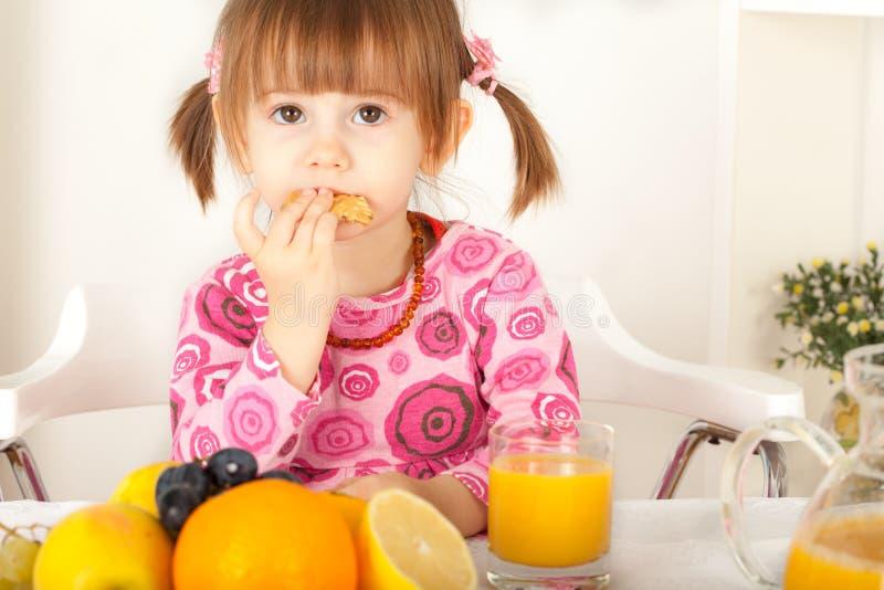 Förtjusande liten flicka som äter kakan arkivfoton