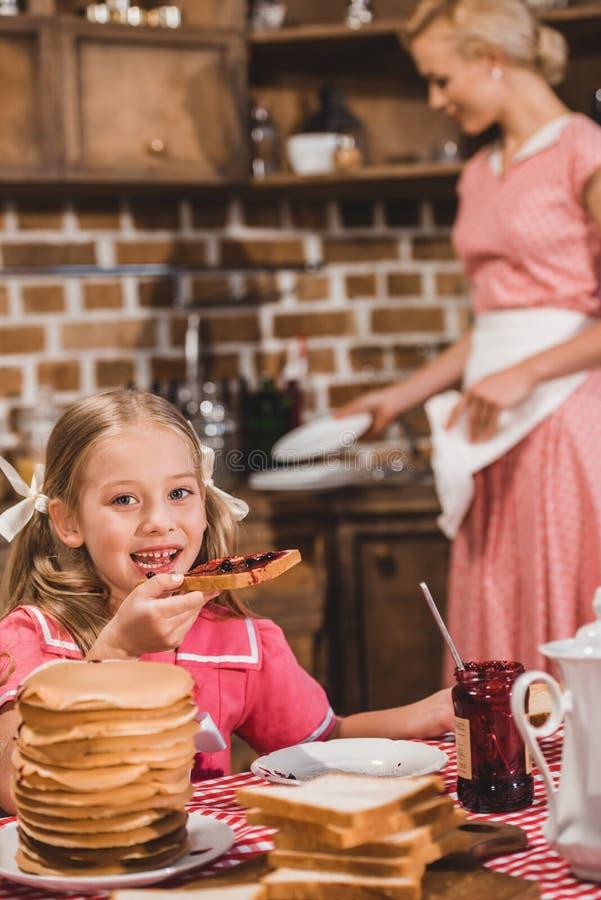 förtjusande liten flicka som äter rostat bröd med driftstopp och ler på kameran medan tvättande disk för moder bakom royaltyfri foto