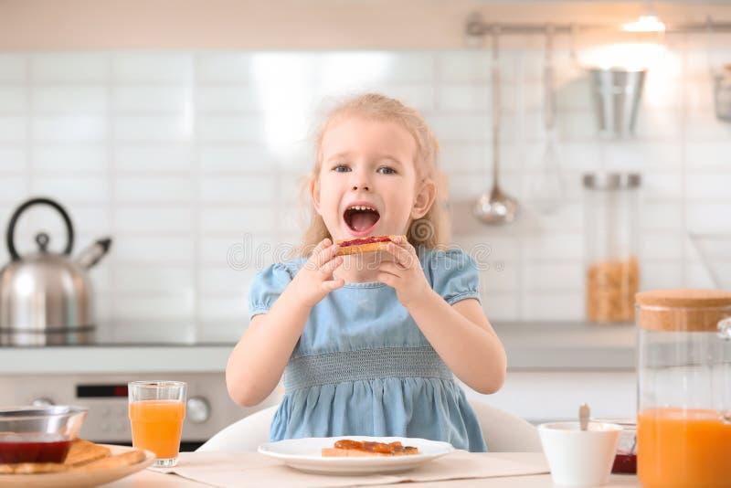 Förtjusande liten flicka som äter smakligt rostat bröd med driftstopp royaltyfria foton