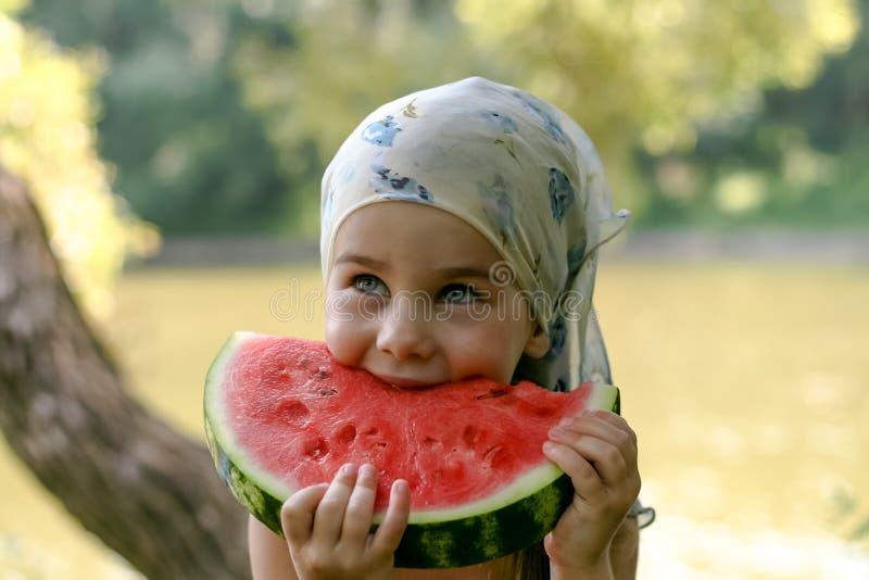 Förtjusande liten flicka som äter vattenmelon royaltyfri bild