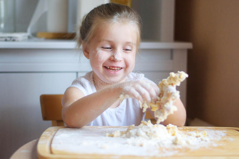 Förtjusande liten flicka som gör degen för pasta fotografering för bildbyråer