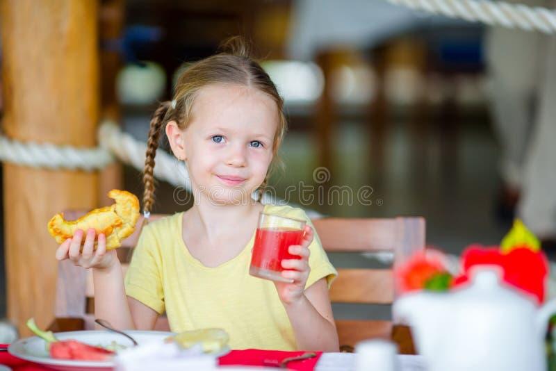 Förtjusande liten flicka som har frukosten på det utomhus- kafét fotografering för bildbyråer