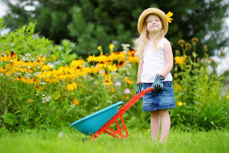 Förtjusande liten flicka som har gyckel med en leksakskottkärra royaltyfri fotografi