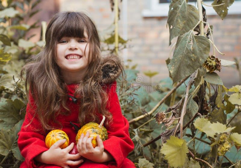 Förtjusande liten flicka som har gyckel på en pumpalapp på härlig höstdag utomhus arkivfoton