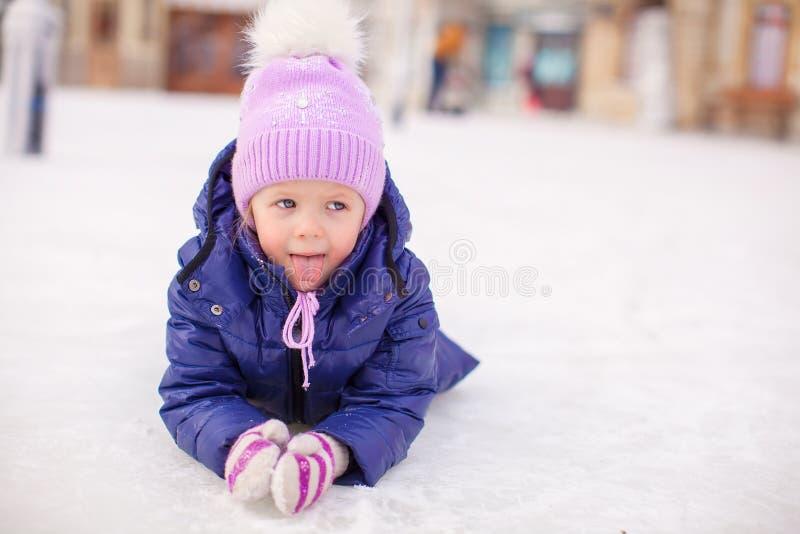 Förtjusande liten flicka som lägger på att åka skridskor isbanan after arkivbilder