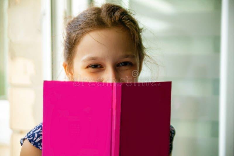 Förtjusande liten flicka som läser en bok i hennes hem arkivbild