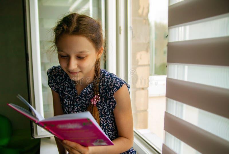Förtjusande liten flicka som läser en bok i hennes hem arkivfoton