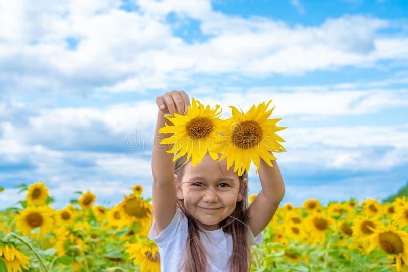 Förtjusande liten flicka som rymmer solrosor i trädgården Closeupungeståenden, behandla som ett barn med två solrosor Begrepp av  royaltyfri fotografi