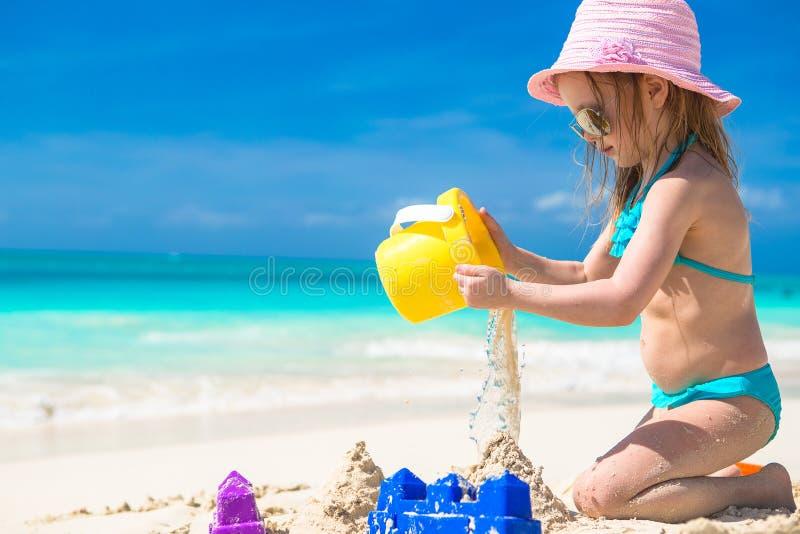 Förtjusande liten flicka som spelar med sand på a arkivbild